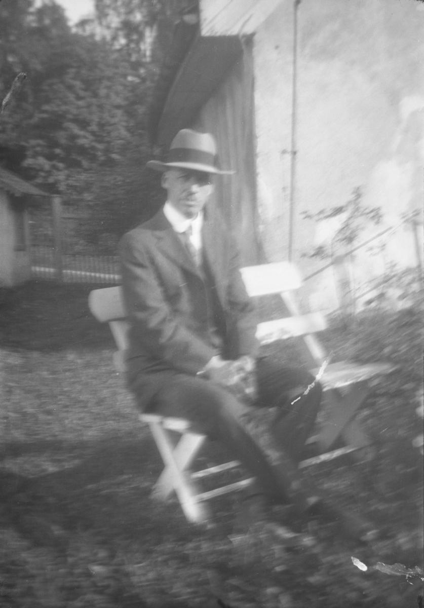 Mann på stol i hage.