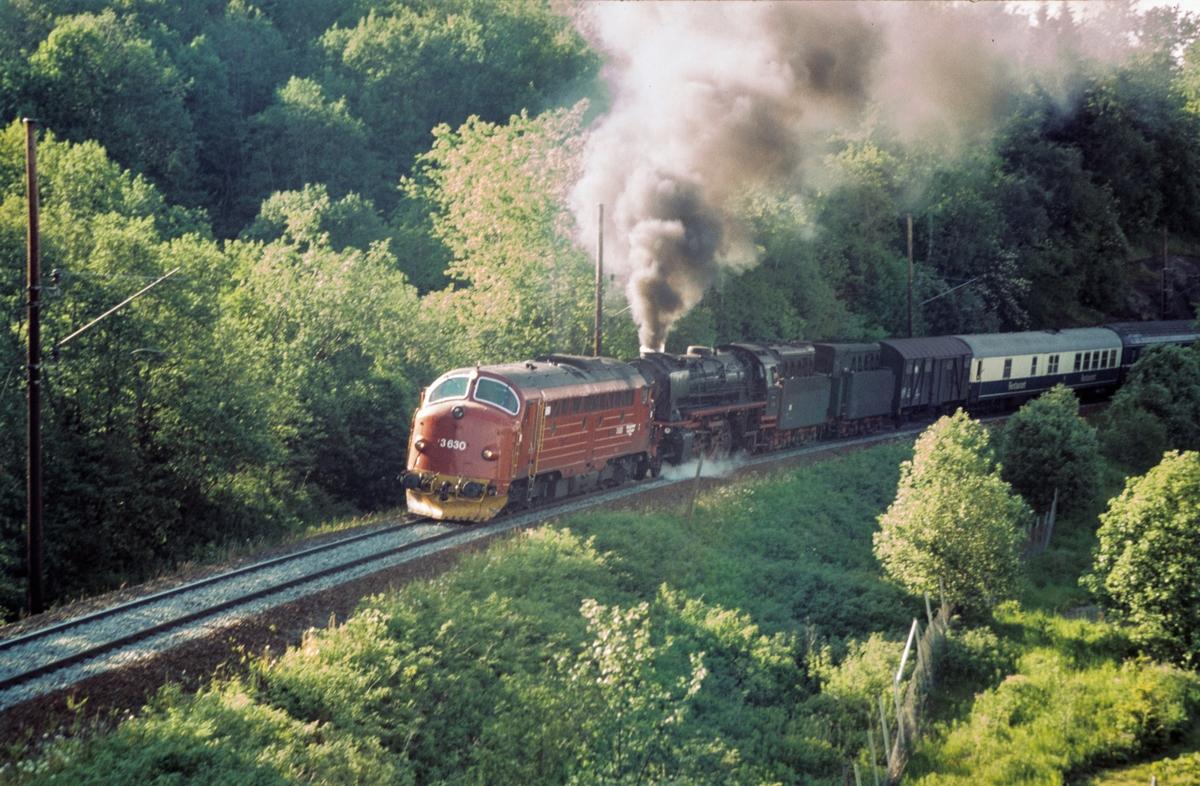 Et tysk reiseselskap på besøk i Norge med eget tog, her underveis fra Trondheim retning Oslo. Toget trekkes av tysk damplok DB BR 41 241. I stigningen fra Trondheim til Heimdal hadde toget forspannlokomotiv, diesellok Di 3 nr. 630. Her i Romolslia.