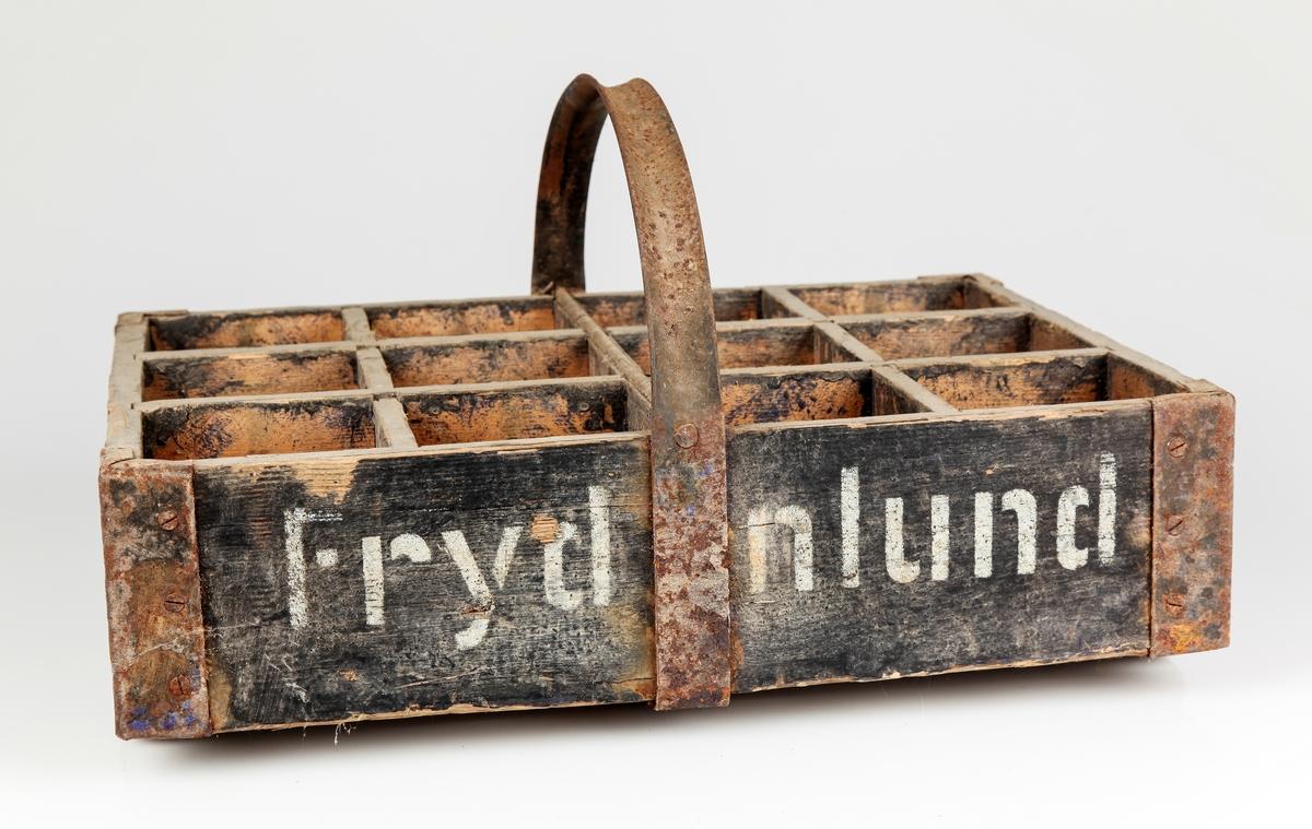 Trekasse med plass til 12 flasker. Jernhank, sprinkelbunn med jernbeslag, beslåtte hjørner. Merket Frydenlund.