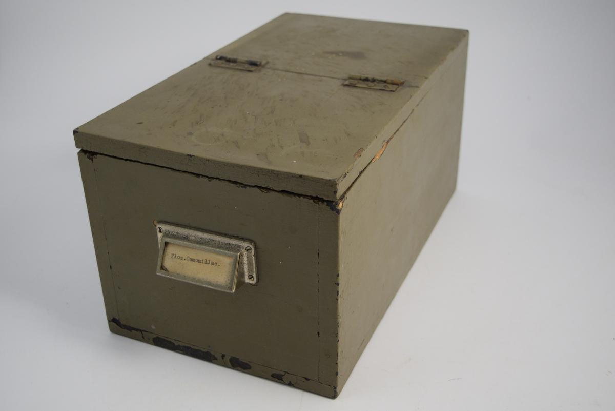2 stk. trebokser med lokk hengslet midt på boksens lengde. Dermed kan halvparten av boksens topp åpnes, mens den andre halvparten er lukket. Boksene ble brukt til oppbevaring av medisinplanter. Flos camomillae betyr kamilleblomst. Cort. quillaya betyr såpebark.