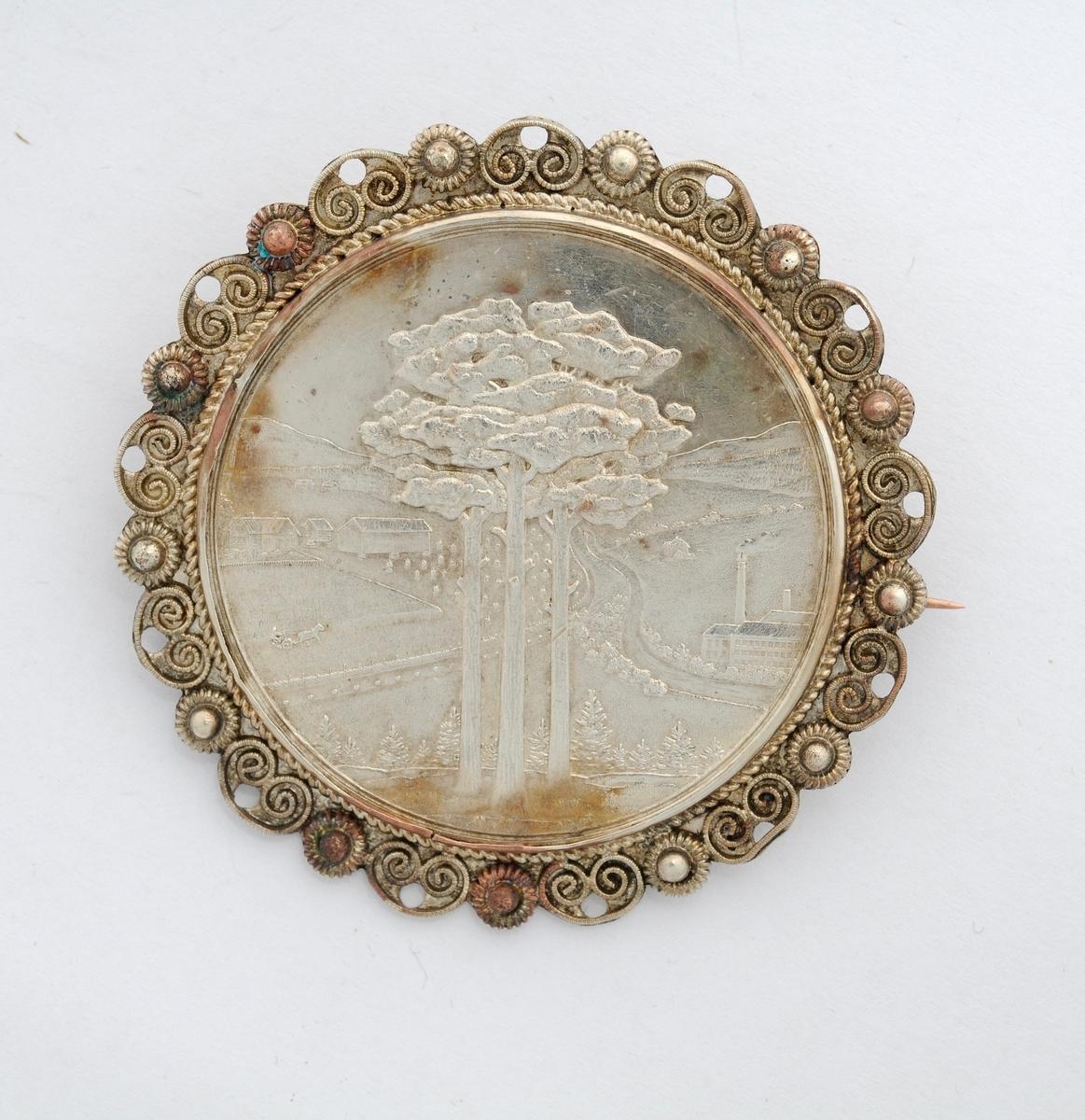 """Sølje, medalje, motiv av tre, industri og landskap. Medalja er sett inn i ein støypt ring i sølv som er dekorert med filigran (krusar og """"bladnyre"""") rundt kanten på framsida. Moderne nål og krok på baksida. Merka med tekst på baksida."""