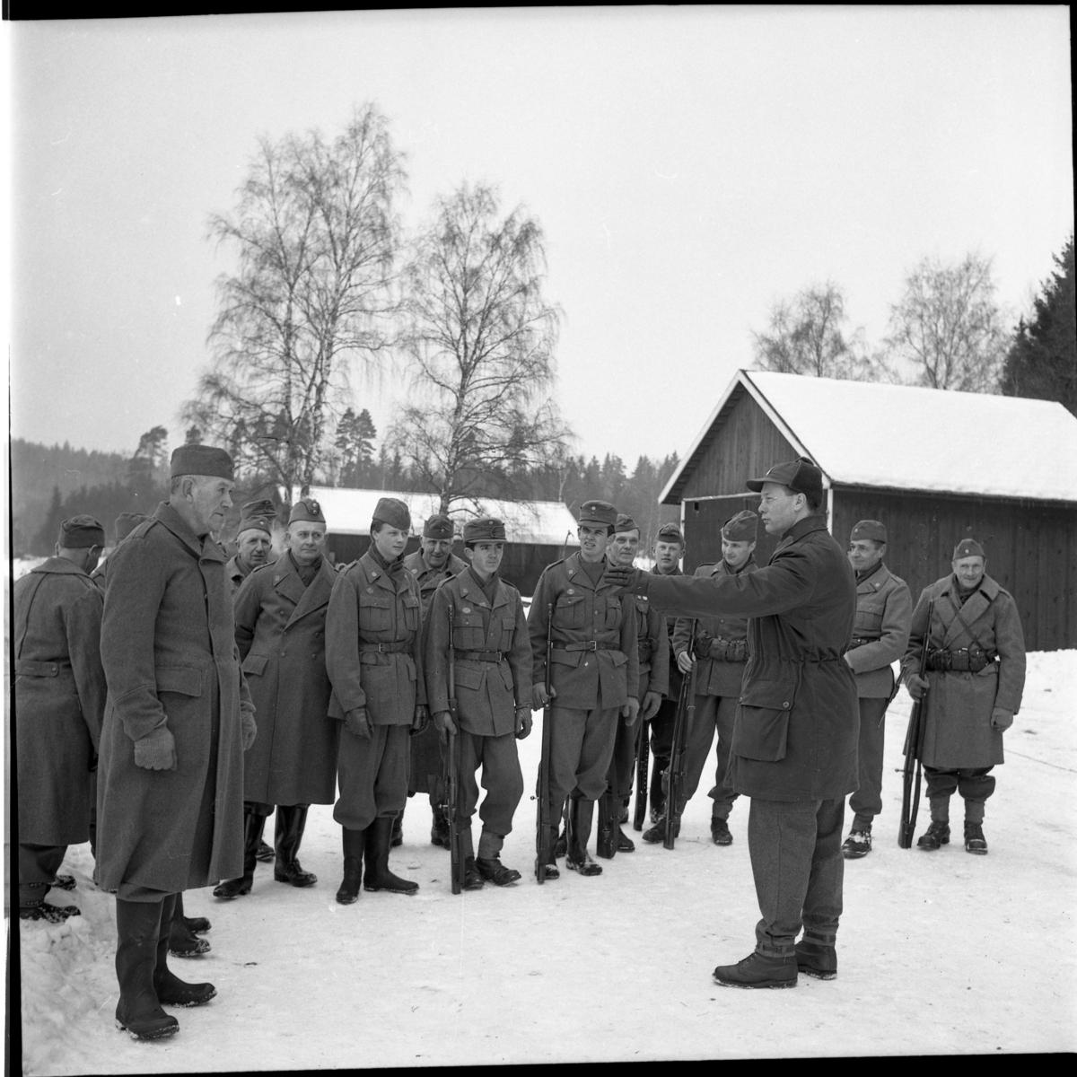Hemvärnsövning vid Örserumsbrum, vintertid. Ett led med uppställda hemvärnsmän, trea från höger är Jörgen Karlsson (Rangenstedt). Framför dem står två befäl mittemot varandra och samtalar.