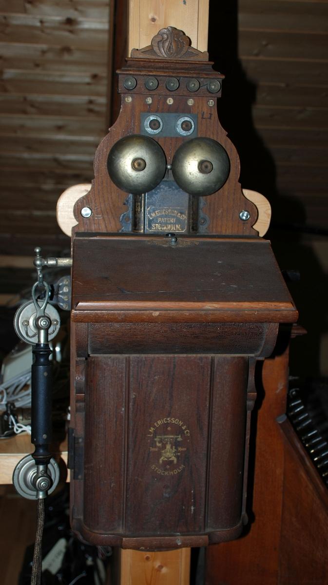Vegghengt telefonapparat med sveiv og telefonrør som henger på gaffel ved siden av telefonen. Mørkbeiset tre. Telefonen er bygget på en treplate med profilerte kanter og dekor øverst. Selve apparatet har tekst på treplaten og er hengslet på høyre side. Nøkkelhull på venstre siden av øvre del av telefonen.
