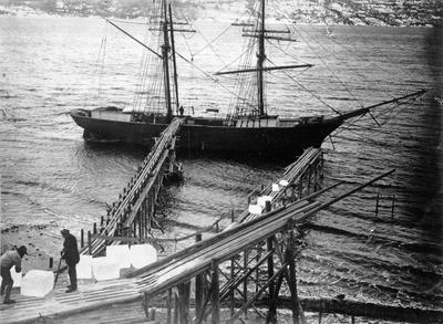 Svart-hvitt foto av fartøy med to master, i forgrunnen to mann som laster is ombord.