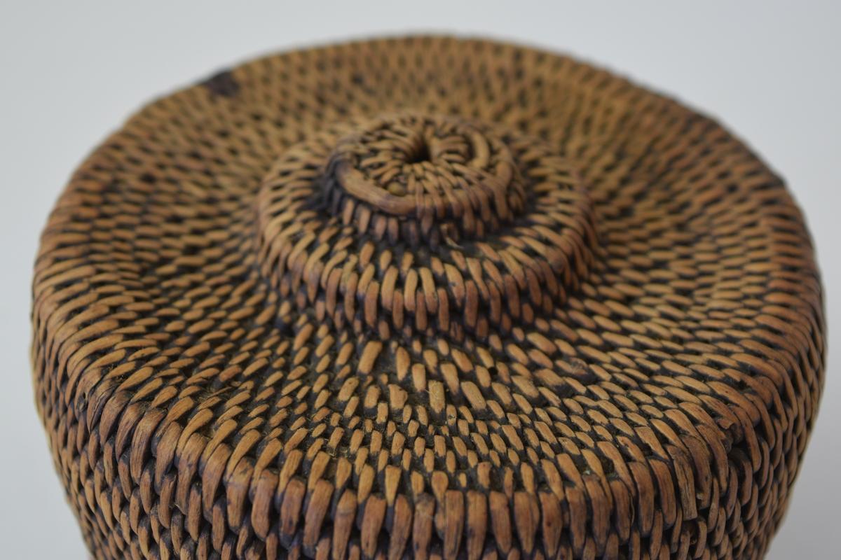 A. Eske. Tegerfletet, brun, plan, sirkelrund bunn, vertikal side.   B. Lokk, Tægerflettet, brunt, sirkelrundt, toppflaten har to avtrappede sirkelformete skiver.