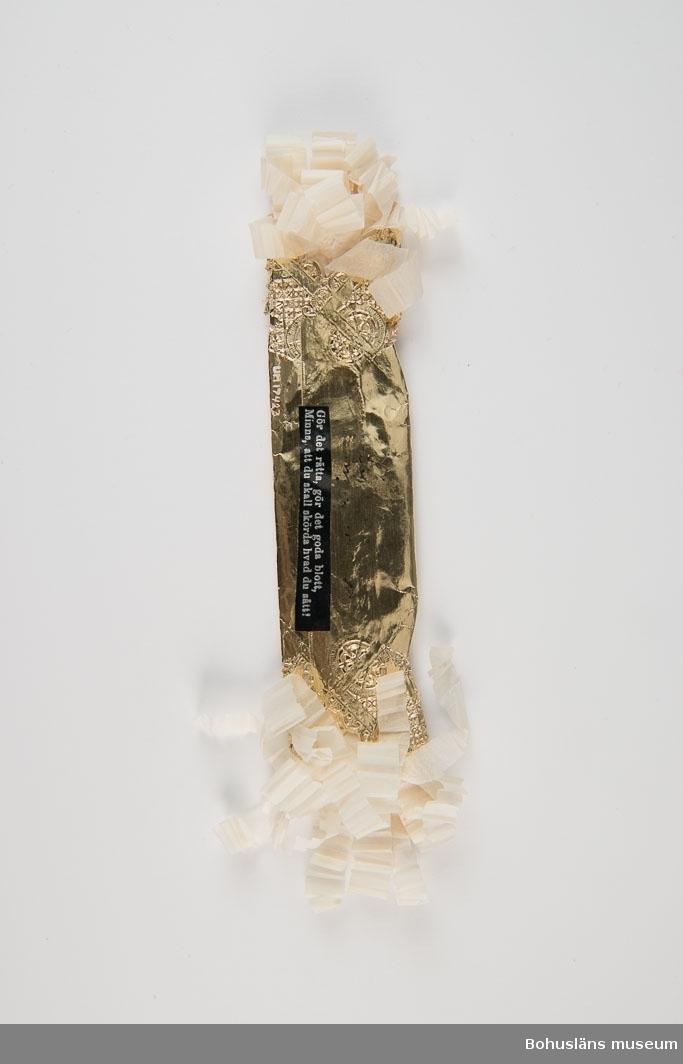 """Präglad av guldpapper. Klippta veckade vita fransar. Tryckt text på påklistrad lapp: Gör det rätta, gör det goda blott, minns, att du skall skörda hvad du sått!  Skrivet med bläck: """"Minne från mammas begravning d 16/1 1936""""."""