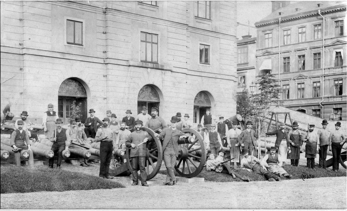 Grupp av hantverkare utanför tyghusets (Armémuseum) östra del vid kanonerna.