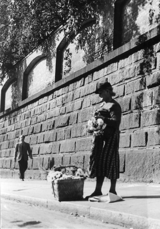 Blomsterselgerske, Pilestredet, Oslo, ved muren til Rikshospitalet, 1950.