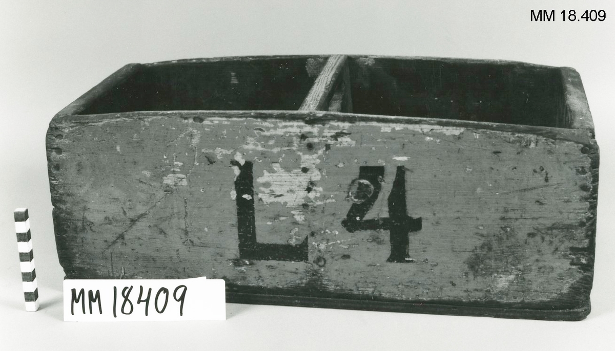 """Verktygslåda, rektangulär form av trä, sammanspikade sidor. I mitten delas lådan av en tvärgående vägg som bildar två sektioner. Handtag utsågat i skiljeväggen. Utvändigt målad i gult med beteckning på ena långsidan: """"L4"""". Invändigt målat i svart."""