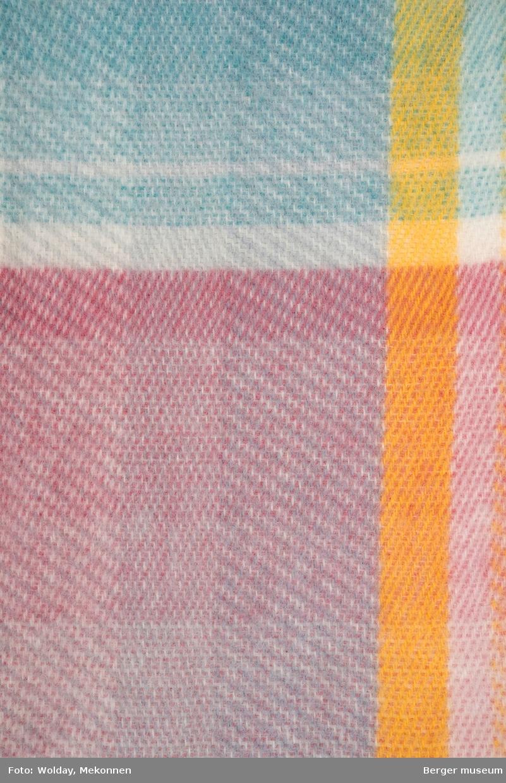En pleddprøve i rutemønster, og avklippet kant på ene kortside. Prøven er sydd langs de tre resterende sidene. Prøven har fire langsgående felt i forskjellige farger, og sju-åtte tverrgående. Fargene er holdt i duse pastellfarger.