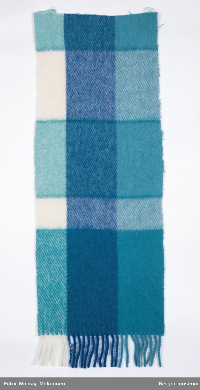 En pleddprøve i rutemønster. Prøven er klippet på begge langsider og en kortside, den andre kortsiden har frynser.  Mønsteret karakterisereres av rutemønster av store rektangulære felt avgrenset med en mørkere stripe vertikalt og horisontalt.