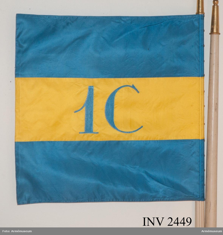 """Av gult/blått foulardsilke. Ett gult fält i mitten, broderat """"C 1"""" med silke. På sidorna blå fält. Doppskon graverad """"1  cykelbrigaden"""". Fäst på standarstån med spets """"GV"""" = Konung Gustav V:s spegelmonogram. Tillh. blå yllefodral märkt C 1."""