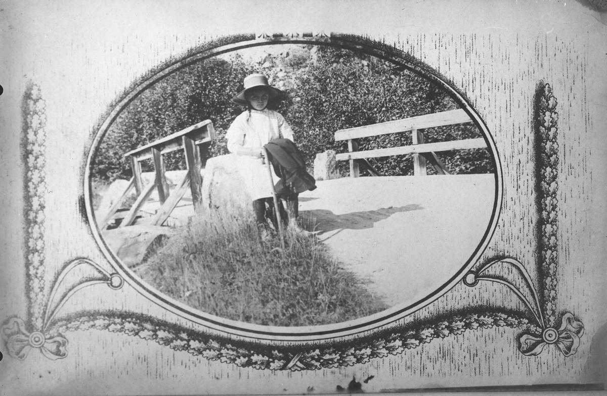 Ovalt bilde av ungjente sittende i landskapsmotiv. Dekor rundt bildet. Montasje på større gjenstand?