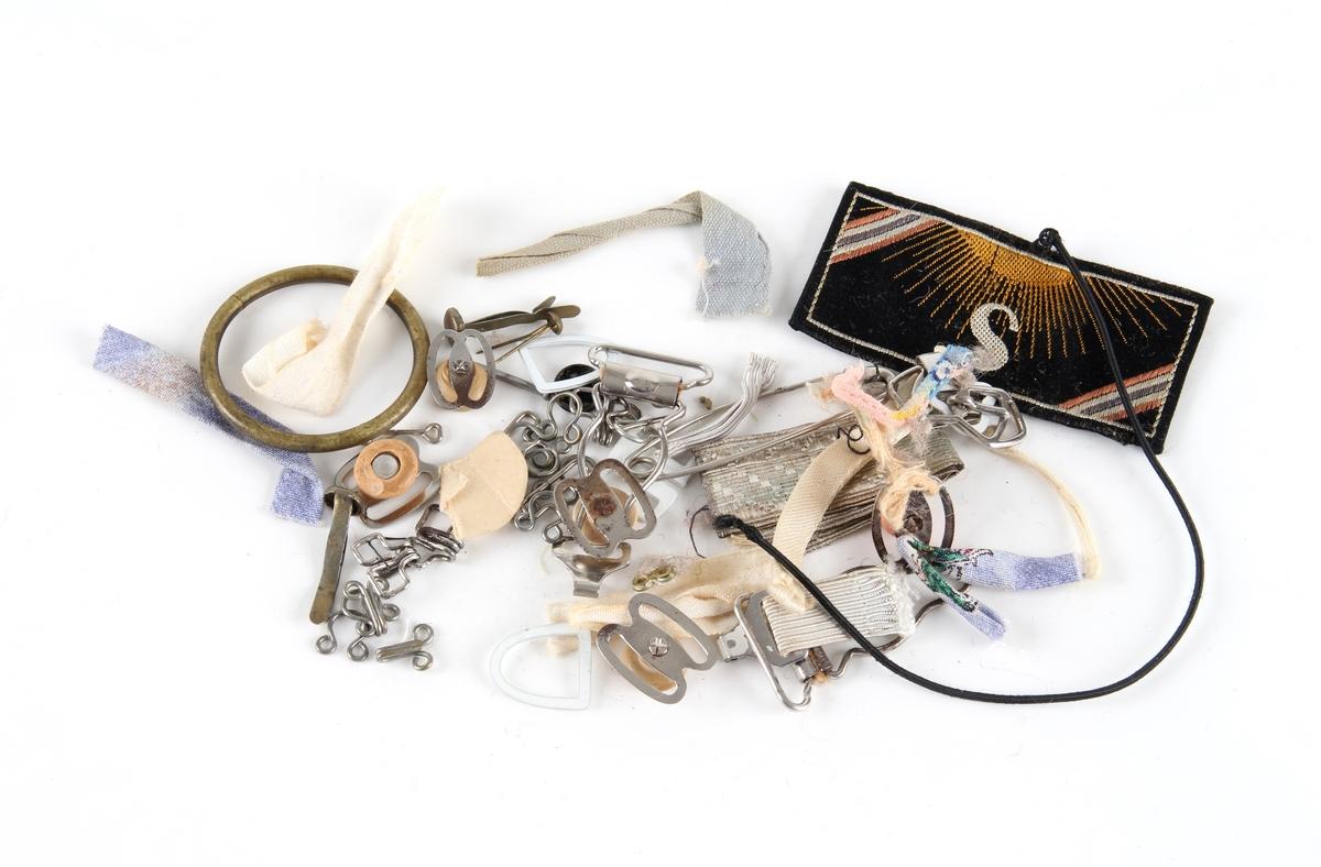 Forskjellige rester som bånd, en spenne, hekter til strømpholdere, tøymerker.