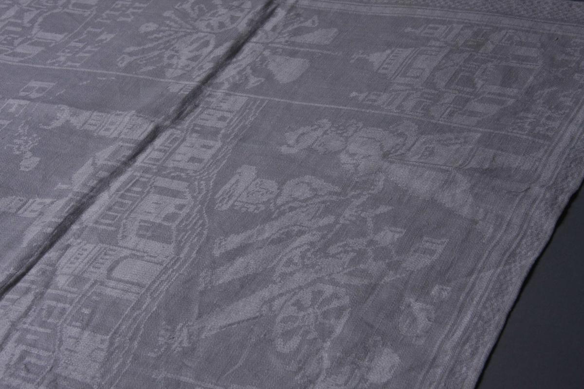 Hvit lindamask med sjakkbrett-bord på langsidene, smalere på kortsidene. Innenfor på langsidene en bord med byggninger med underskrift. Midtpartiet har et bybilde med overskrift og to speilvendte ryttere over. Videre hus og våpenskjold. Servietten har smal fall på kortsidene.