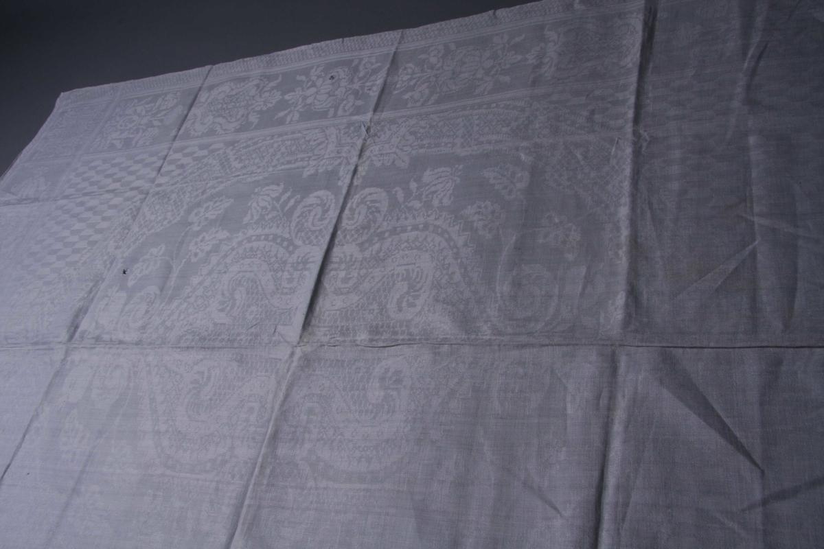 Hvit lindamask med sjakkbrett-bord på langsidene. Innenfor en bred stilisert blomsterbord med enkelte skjold-liknende motiver. Midtpartiet består av et stort dekorativt våpenskjold i ramme av stiliserte blomster og geometriske figurer. Hjørnene er utfylt med rutemønster av trapes-formete figurer. Servietten har smal fall på kortsidene og er merket.