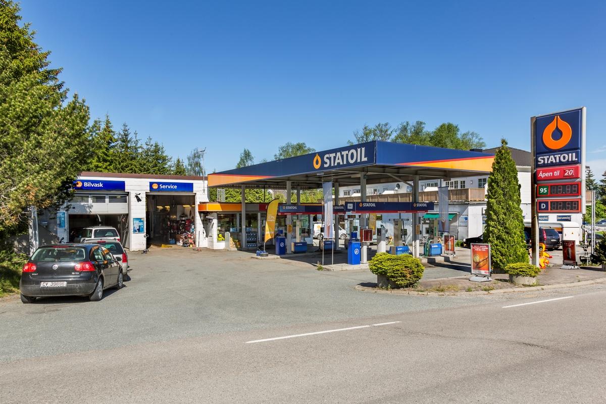 Statoil Hemnes. Bensinstasjon med veiskilt Statoil. Pumpetak bensinpumper verksted vaskehall og butikk. Beplantning mot veien. Parkerte biler.