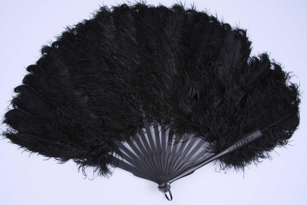 Av strutsefjær, sort med trespiler med stiliserte motiver skåret inn i spilene. Metall-hempe.
