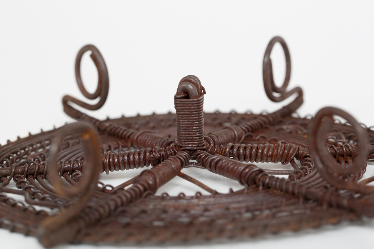 Rund gryteunderlag med håndtak og seks bein, laget av ståltråd.