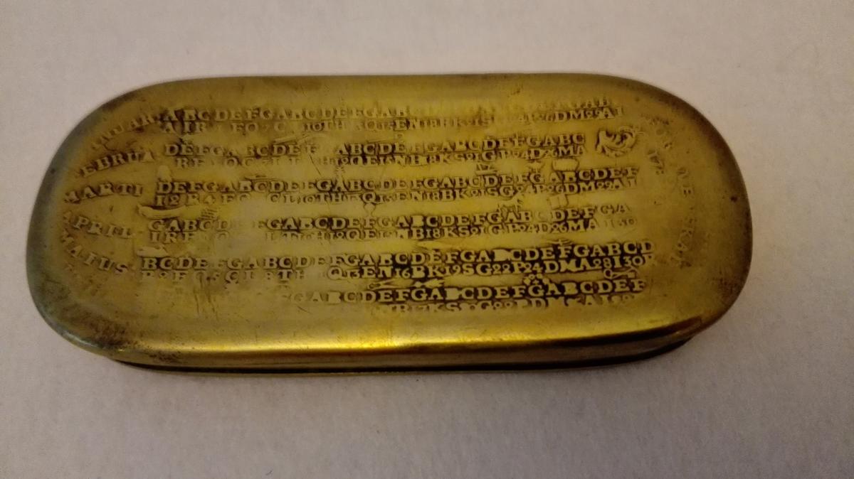 1 tobaksdaase av messing.  En saakaldt svensk almanakdaase fra 1787. Kjøpt ved lensmand Erik Seim, Aardal.