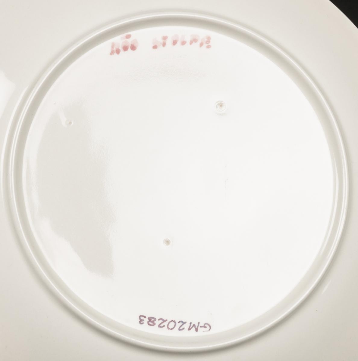"""Tallrik, flat, av flintgods, formgiven av Berit Ternell för Gefle Porslinsfabrik, förmodlig modell -BT. Rund med upp- och utvinklat brätte, keplös. Rund fotring. Dekor """"Poral"""" av Ternell, två handmålade band på brättet, matt blå och röd, över detta svart, spetsig stämpeldekor mot vit glasyrfond. Matt röd text under """"Röd Stolpe""""."""