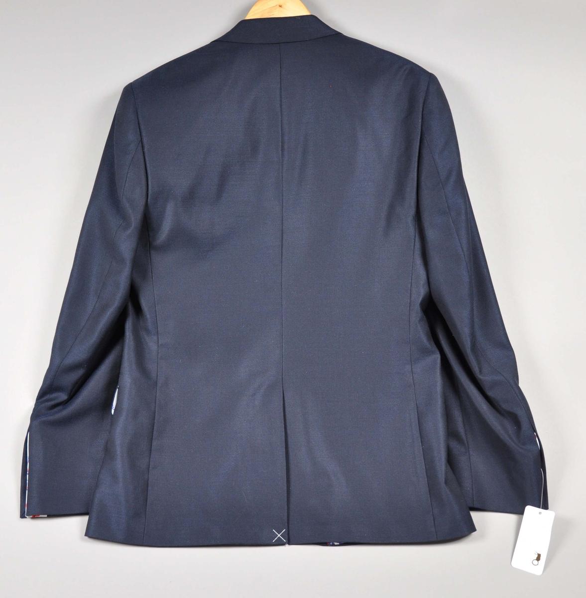 """Mørkeblå dressjakke av ull/silke, foret med samme silkestoff som i damekjolen og tørkleet, et hvitt silkestoff med """"rosemalt"""" mønster. Jakken har fire innerlommer, en med knappelukking. Utvendig to jakkelommer med klaff foret med silkestoffet, en brystlomme med påbrodert """"traktorlogo"""", Mørkeblått kantebånd fra kraven og ned. Lukket med en stor stoffknapp på ermene, fire ganger to mindre stoffknapper i hvitt (2), rødt og blått. På høyre erme brodert:Heia Norge i henholdsvis rødt og hvitt. Str.:48"""