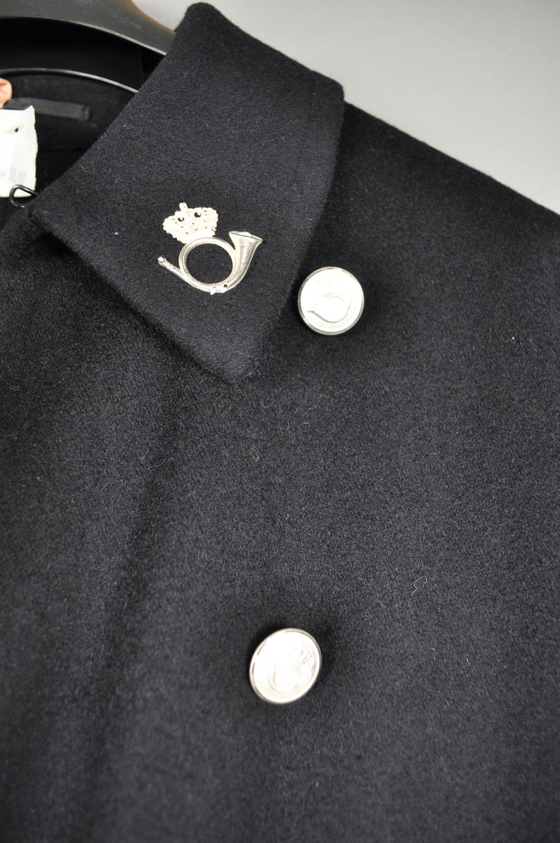 Lang uniformsfrakk med spensel bak. Frakken er sort med sølvfargede postlogomerker og knapper.