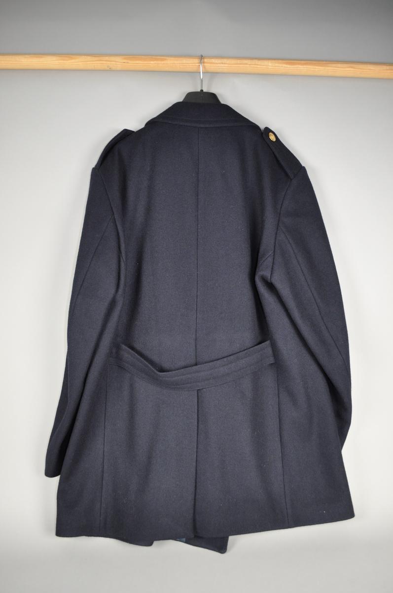 Mørke blå jakke/pjekkert med stikklommer og skulderklaffer. Spensel i ryggen.