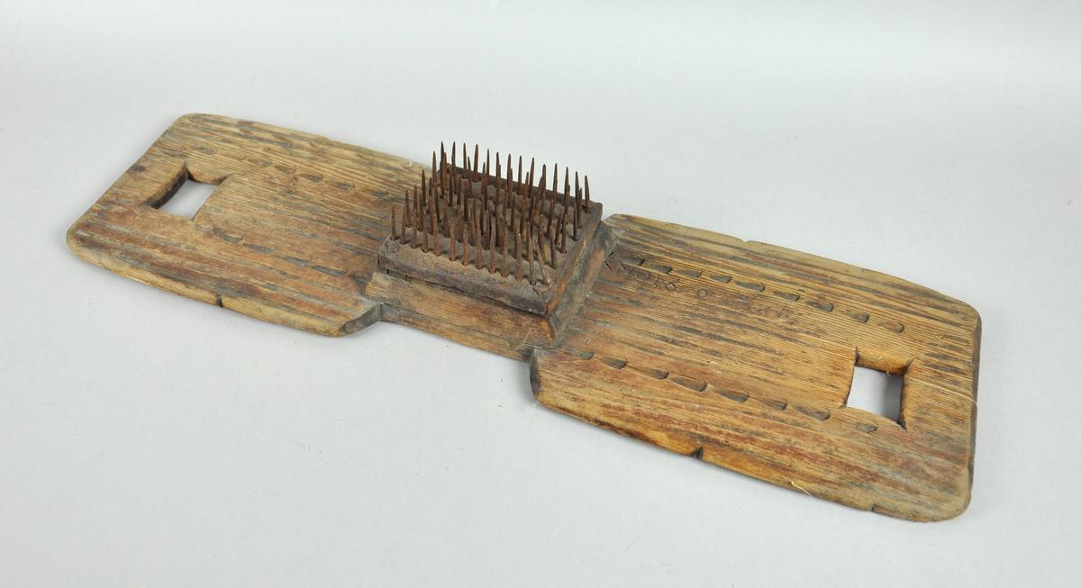 Hampehekle av tre med kvadratiske hull i hver ende. På midten er det festet en trekloss med stålnagler.