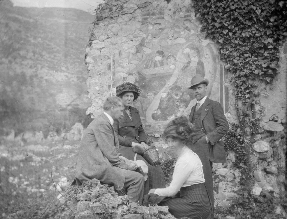 To kvinner og to menn på utflukt, fotografert foran en vakker steinmur