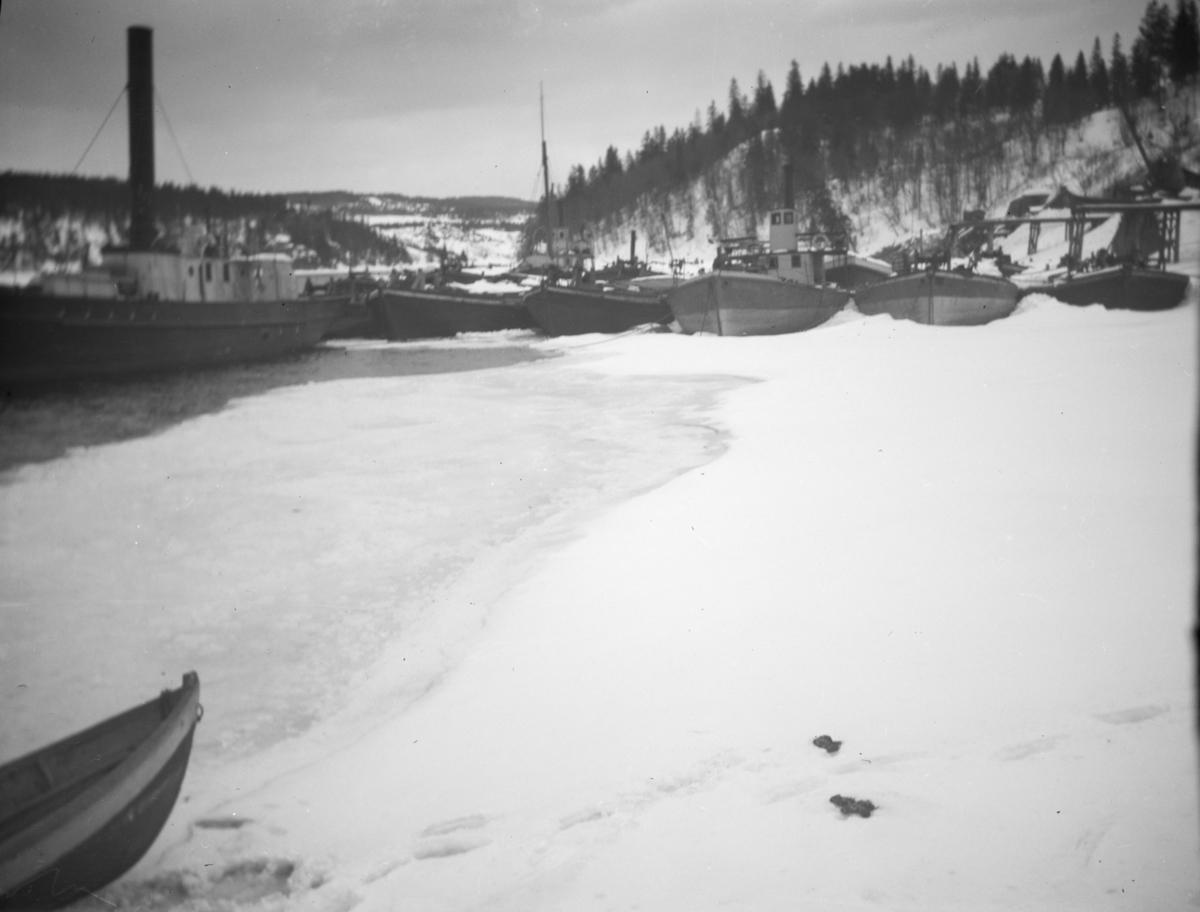 Båter i opplag i vika på Minnesund vinterstid, i forgrunnen D/S Thor, i bakgrunnen D/S Industri II og Industri samt lektere