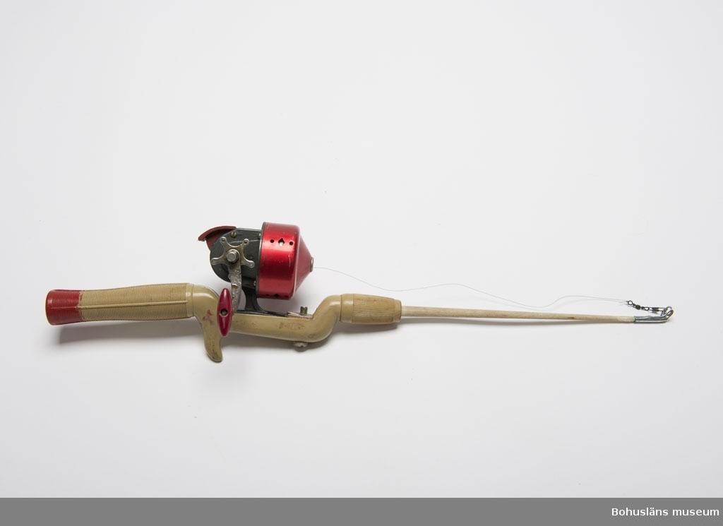 """Spö av grön-grått konstmaterial. Rött längst bak på handtaget. Inpressad text: """"RECORD"""". I spöspetsen är det en metallhylsa med en en ring som linan skall löpa genom. Röd och grå inkapslad haspelrulle med vevhandtag. Märke: """"BELLY No. 58""""."""