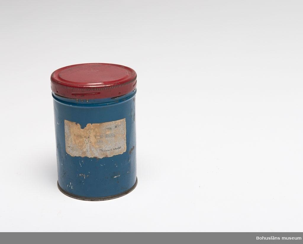 """Blå med rött lock. Nästan oläslig etikett med rest av silverfärg - i nedre högra hörn står det """"Latest Model"""". Inuti är de rund skiva av papp i botten. Sammanhör med UM023748. Enligt uppgift är detta originalförpackningen. UM023746 - UM023749 hör ihop."""