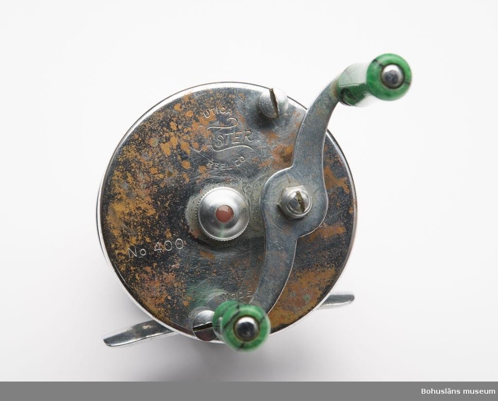 """Två runda metallplattor som är sammansatta parallellt på ca 4,5 cm  avstånd med fem stycken metallstavar. Mellan två av stavarna är det en liten smal platta som är en anordning så att rullen kan fästas vid  ett spö. På den står det """"MADE IN U.S.A. PATENTED"""".  På den ena runda  metallplattan står det """"UTICA CASTER REEL CO NO 400 MODEL C"""".  På ena sidan finns en vev med två små handtag med överdrag av svart-  och grönmelerad ureaplast. Rullen skall fästas på ett spinnspö. Lina av cellulosafiber (sk silkelina) behandlad med petroleumprodukt.  Det finns en anordning så att linan fördelas jämt på rullen.  Sammanhör med UM023746 - UM023749."""