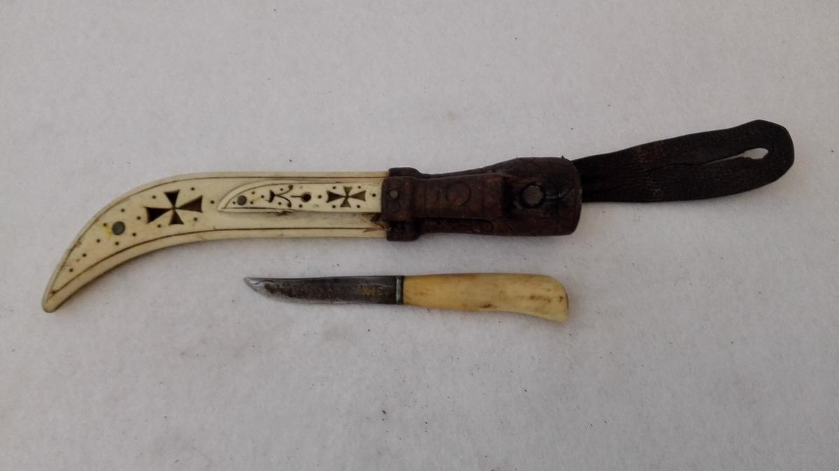 1 dobbeltslire av ben.  Sliren ligner meget no 3668 og er som denne sammensat av to mot nedre ende bøiete benstykker. Kniven til denne mangler. Utenpaa denne er lagt en gjennembrudt forsiret benplate til en mindre kniv. Denne der har hvidt benskaft, medfølger. Den største slire har paa baksiden indridset J.J. og paa forsiden forsirt med et gjennembrudt kors og strekornamenter. I øverste ende skindbeslag.  Kjøpt av John Johnsen Flaam.