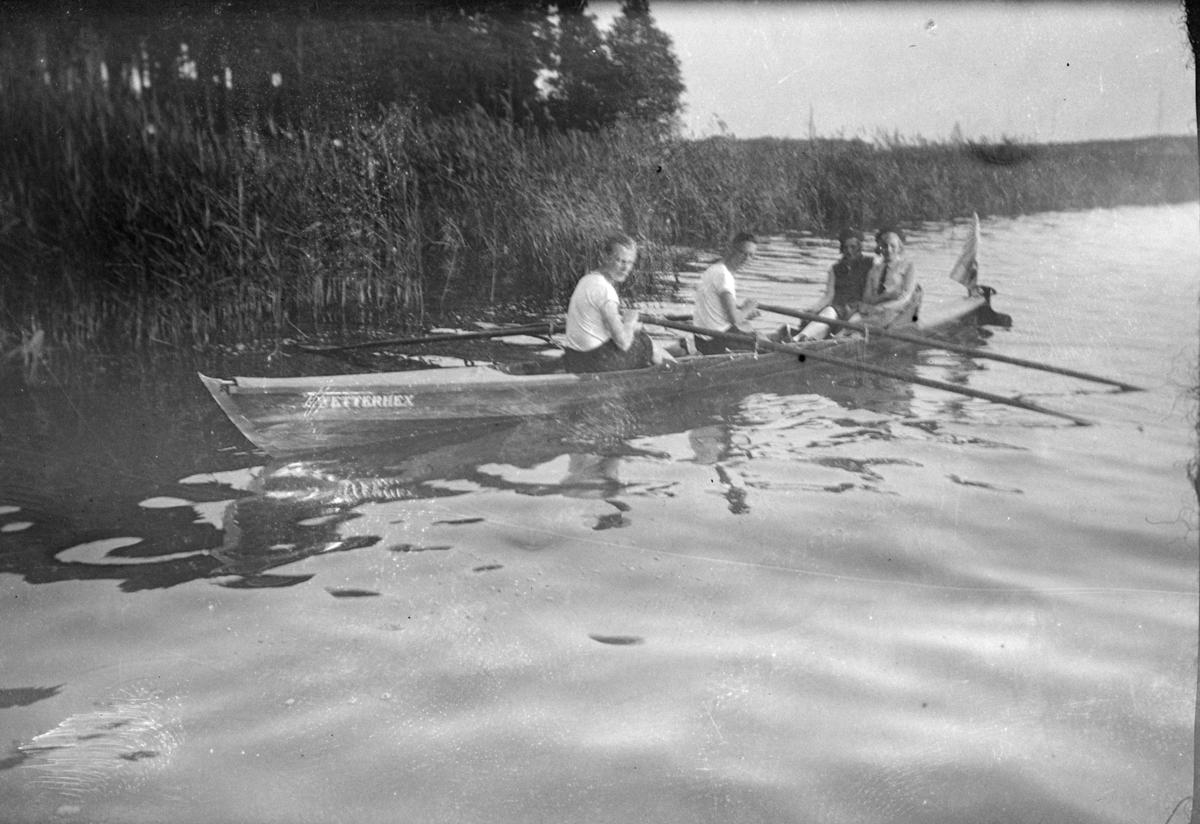 To menn og to kvinner i en kapproingsbåt