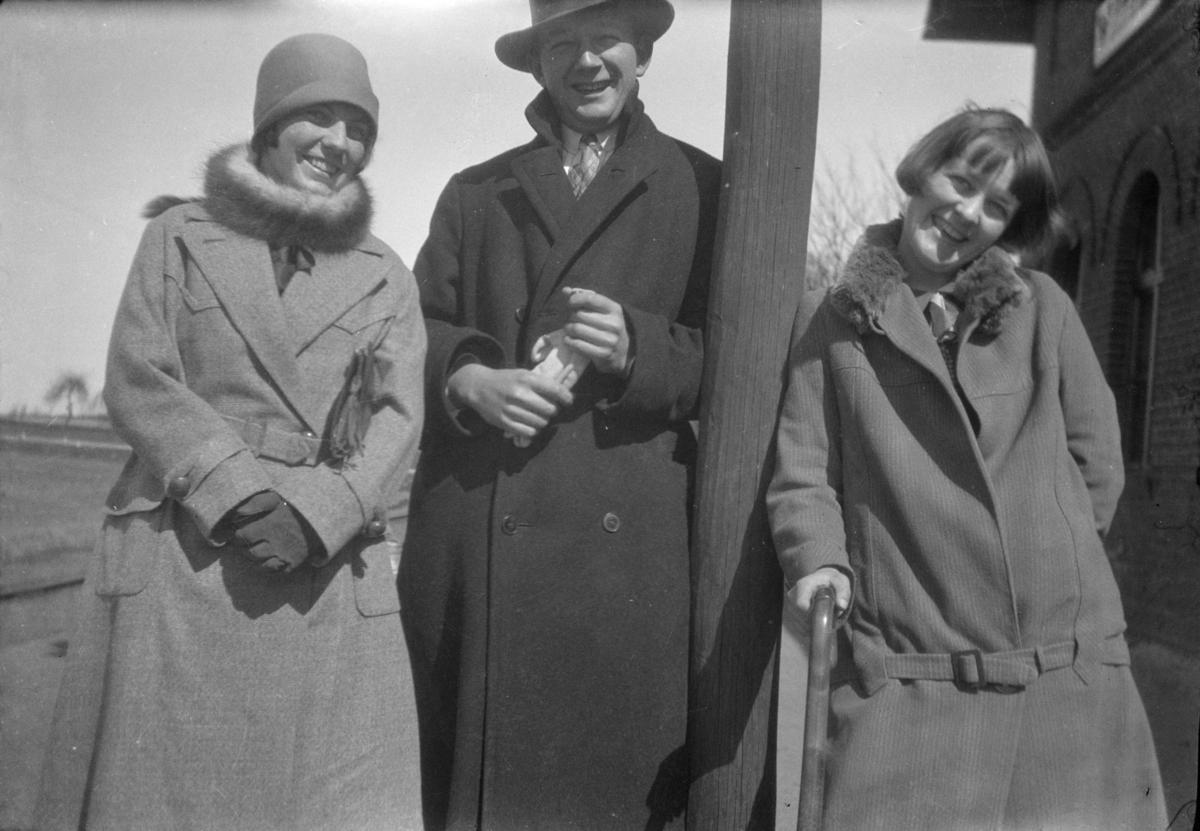 En mann flankert av to kvinner