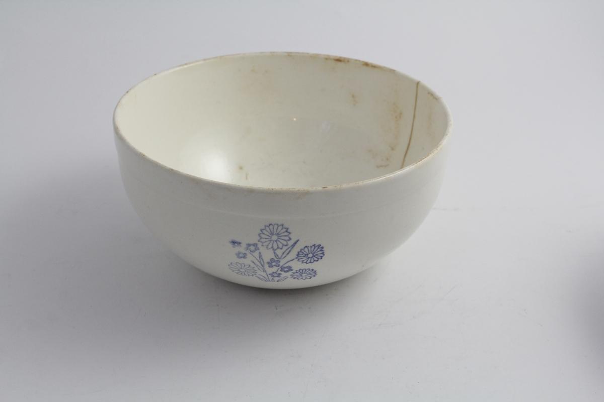 Bolle i steintøy, brukt til matlaging/husholdningsbruk. Hvit bunn med blå dekor. Fire blomsterbuketter jevnt plassert på utsiden.