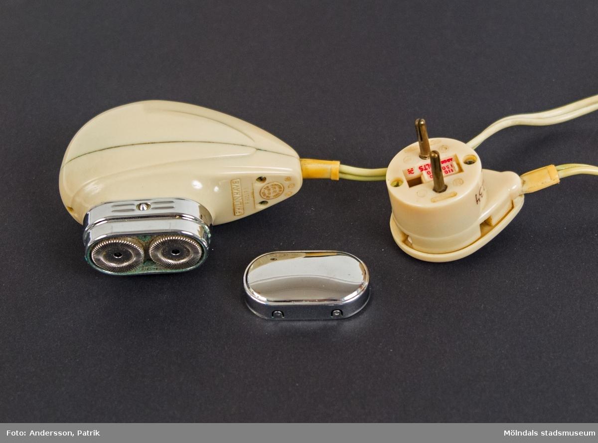 """Elektrisk rakapparat tillverkad av Philips från 1953. Rakapparaten är av vit plast och har två roterande knivblad med skyddslock av förnicklat stål.  Gjutet i plasten finns texten: """"PHILISHAVE PHILIPS 7753 110-130V-0W AC-DC 20' MADE IN HOLLAND"""" . Rakapparaten har... lång strömsladd. På stickkontakten finns texten: """"PHILISHAVE"""", gjuten i plasten."""