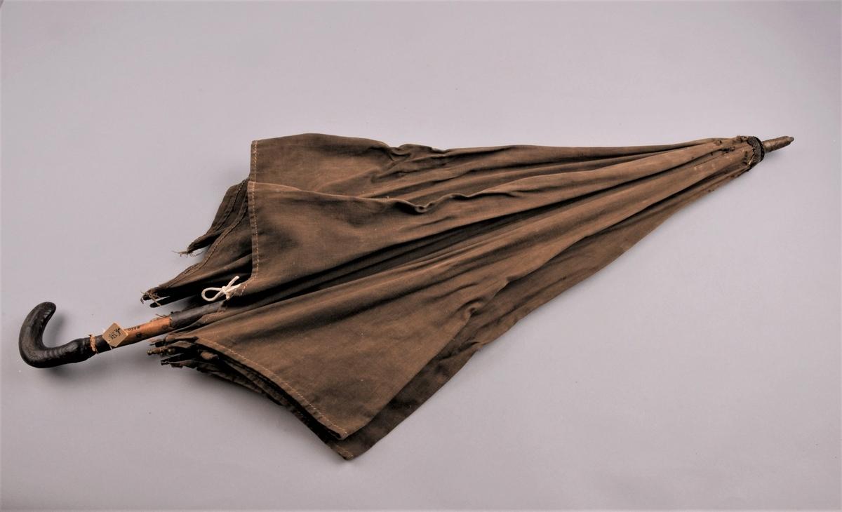 Paraply i brungrønt stoff med metallspiler. Skaft av tre,handtak av tre trekt med skinn. Topp av messing. Endane på metallspilene er også i messing.