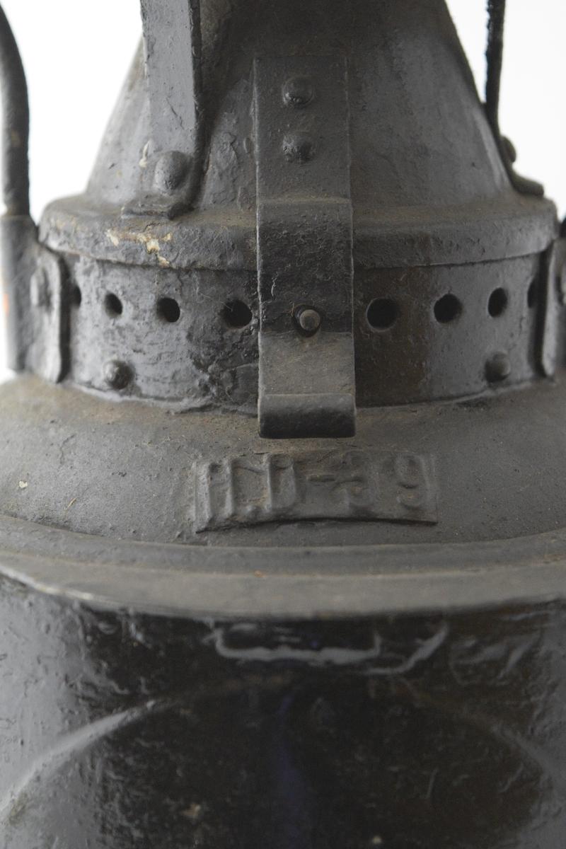 Parafinlampe. Sylindrisk hovedform med ett rødt og ett hvitt glass (buede, med optisk linse: fresnel) på motstående sider. En luke kan åpnes mellom glassene for å tenne lampen. Fire rektangulære ben nederst, avrundet hank øverst. Brukt som sluttsignal ved jernbanetransport - hang på siste vogn i toget. Lyste rødt bakover og hvitt fremover. Rundt lampehatt med innskrift.