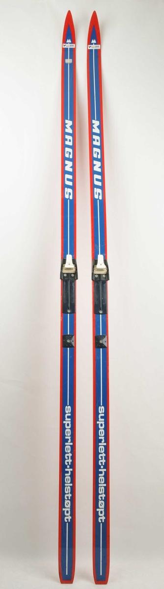 Langrennski laga av glasfiber. Raude, med blå og kvit dekor på oversida. Namnet MAGNUS skrive i store kvite bokstavar framme på skia. Påsatt Salomon bindingar i plast.