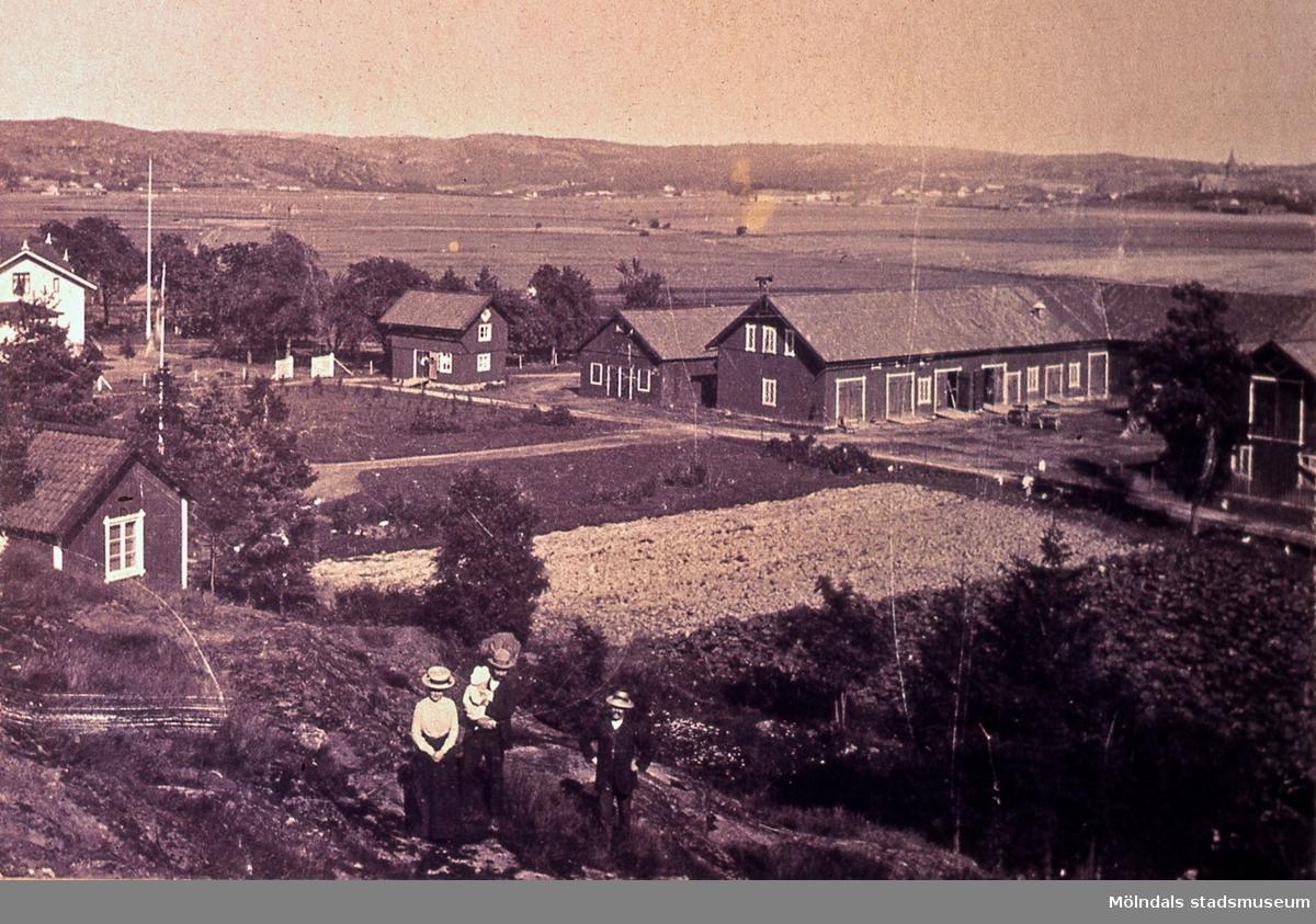 Vy från Prästgården i Fässberg mot kyrkan i Mölndal i början av 1900-talet. Ernst och Hildur Wallmark samt sonen Folke ser ut över nejden.