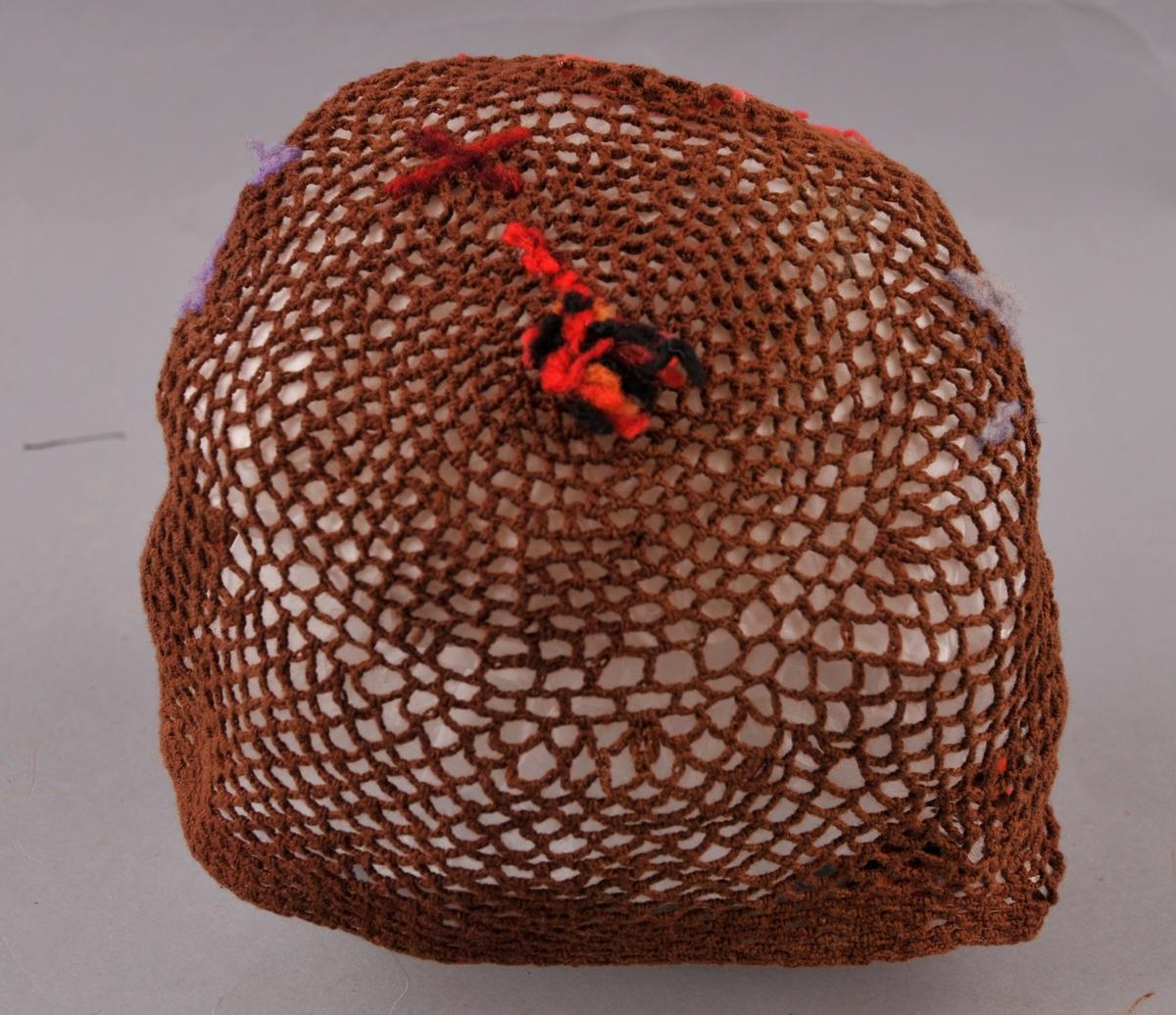 Luve hekla av luftmasker. Langs framkanten er det sauma (med vevsaum) inn tre åttebladroser med ikatfarga garn i raudt, fiolett og orange. Rundt framkanten er det sydd flosskant i raudt, brunt, svart og gult ullgarn. Eiin dusk i samme garn og fargar er festa ved issen. Framom dusken er det sauma ein rett strek og eit kryss (Andreaskross). Eit kvitt bendelband er sydd fast i venstre sida.