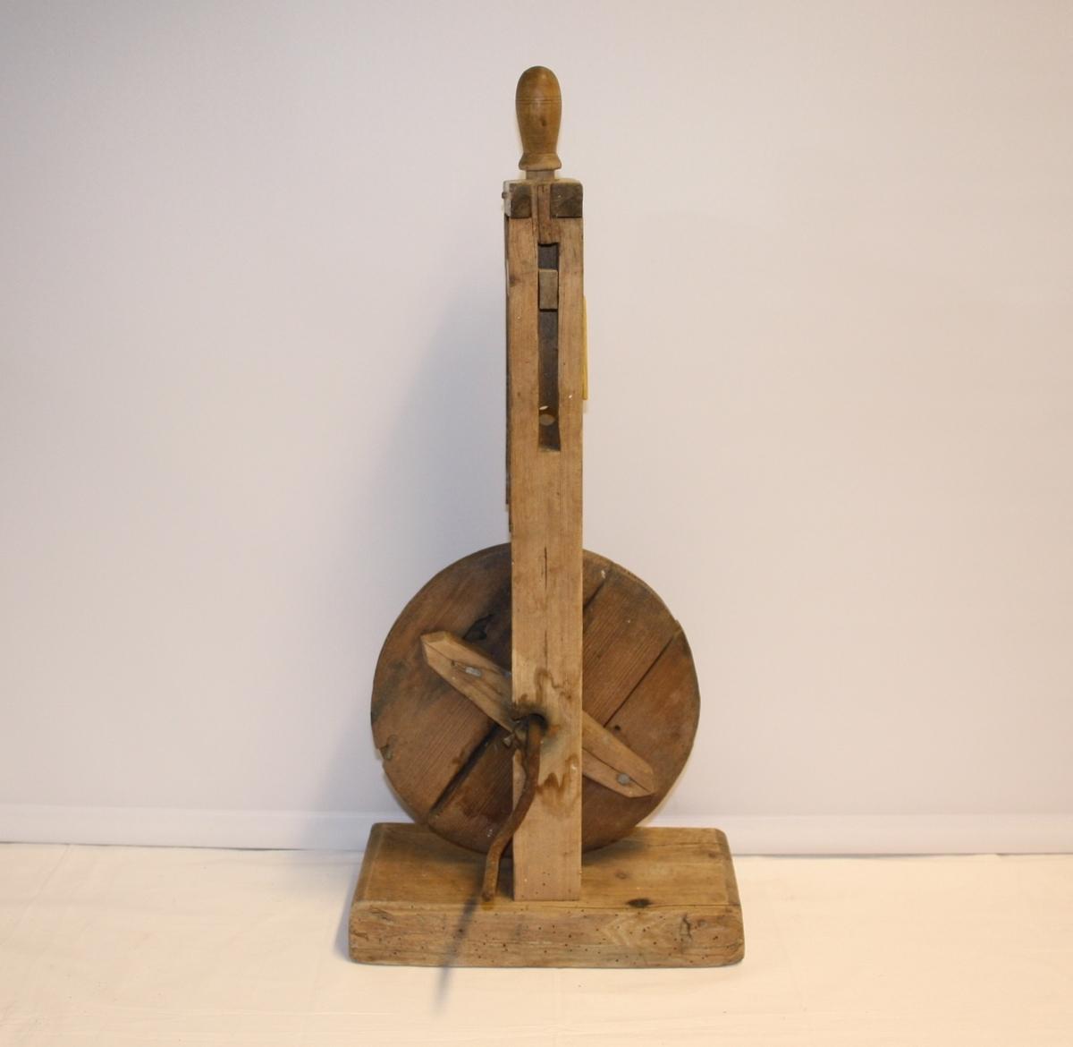 Spolehjul, bordmodell. Vertikalt montert spolehjulmed sveiv i og står på ein trekloss.