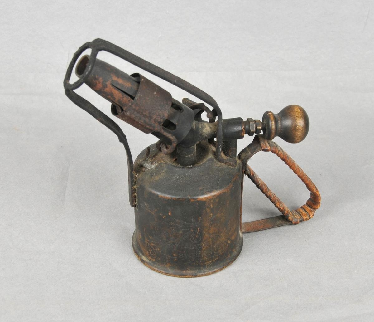 Liten behaldar med handtak surra med tæger. For bensingass. Blei varma upp med sprit til bensingassen kom ut. Denne loddelampa var i bruk til sylvsmedarbeid fra 1907 og fram til 1920: Då kom bensingass med trøbelg i bruk.