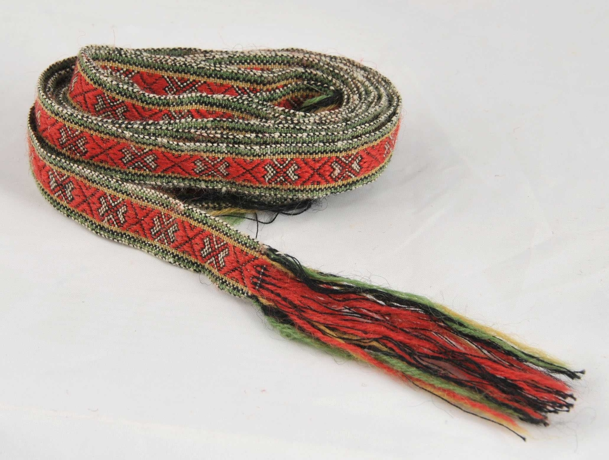 Grindvove band med frynser i båe endane. I renninga er det bruka særs tynn, svart bomulsgarn, og innslaget er hardt slege til.