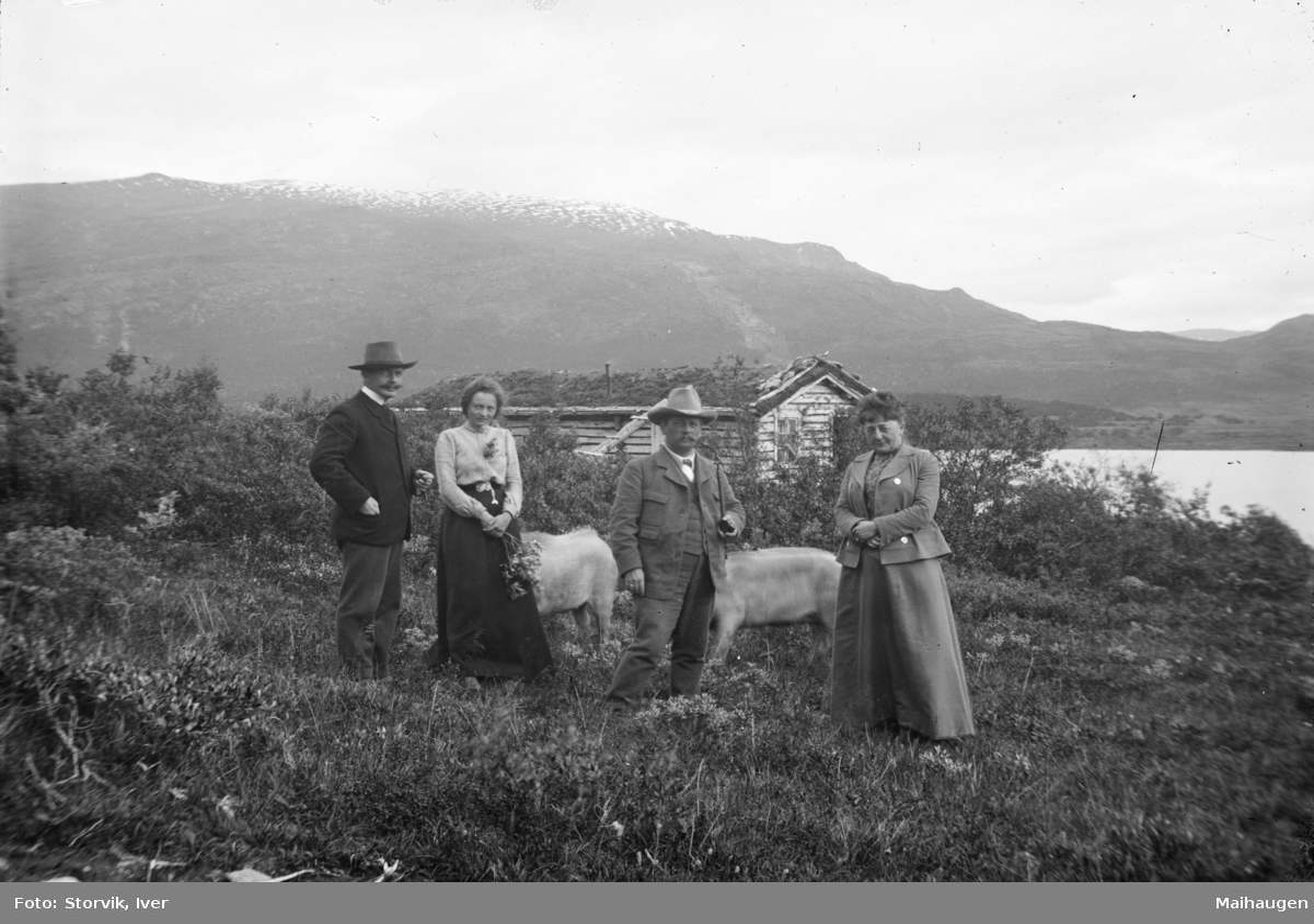 Hytte ved fjellvatn, i forgrunn to menn hvor en med langpipe, to kvinner og glimt av to griser. Mulig fra Sjodalen