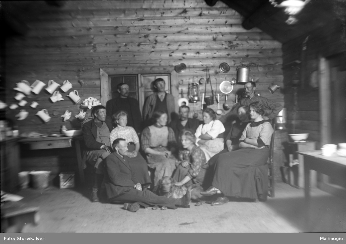 Sjodalen, Bessheim, gruppe kvinner, menn og en hund klar for fotografering på kjøkkenet. Kjøkkenredskap og mugger hengt opp på veggen