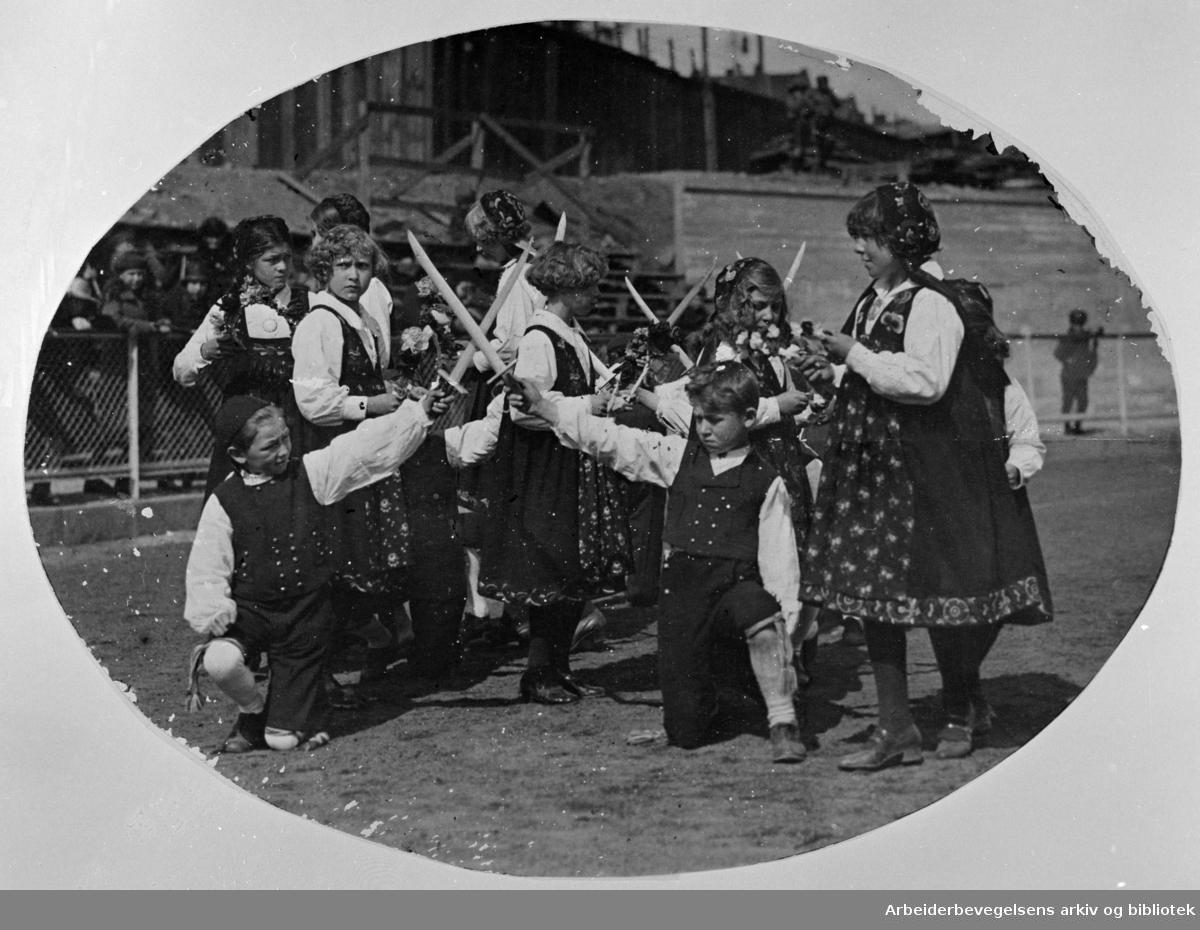 """1. mai 1925, fra barnestevnet på Bislett stadion. Leikarring fra et barnelag som opptrer med dansespillet """"Falkvor Lommanson"""" (Sverddansen, Fakkeldansen)."""